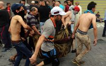 Iraqis evacuate a body from the site of a suicide car bombing claimed by the Islamic State group on July 3, 2016 in Baghdad's central Karrada district.