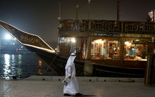 An Emirati man walks past a restaurant boat adorned for the Muslim holy month of Ramadan.