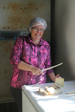 An image of cheesemaker Jo preparing cheese for market day.