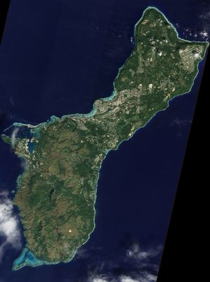 A satellite image of Guam. Andersen Air Force base is in the top-right corner, while the Naval base is on the left.