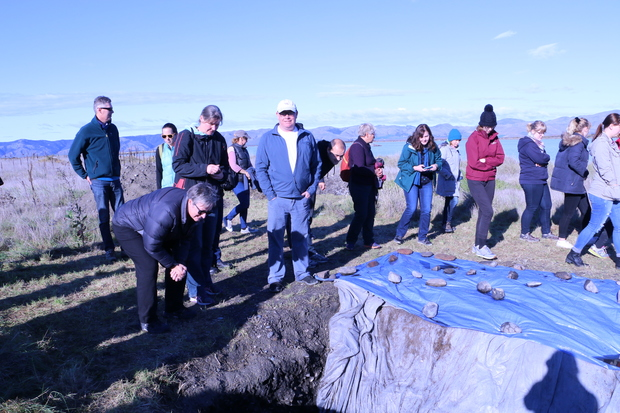 A group of iwi members and archaeologists visits one of six large, ceremonial hangi pits that have been uncovered at Wairau Bar.