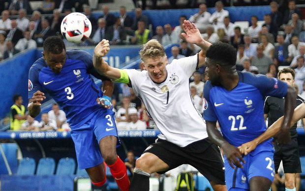 Germany's Bastian Schweinsteiger gives away a penalty as he challenges Patrice Evra.