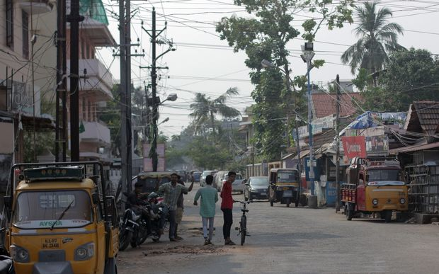 Street in Kerala town with tangled overhead wires,, trees and tuk tuks