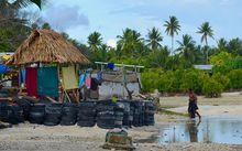 Beach and traditional hut surrounded by wall of tyres