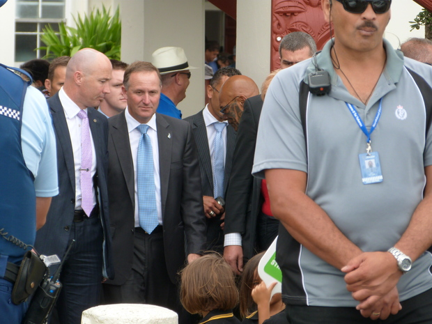John Key leaves Te Tii Marae surrounded by security.