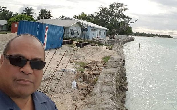 MP in selfie on coast line with houses in the background