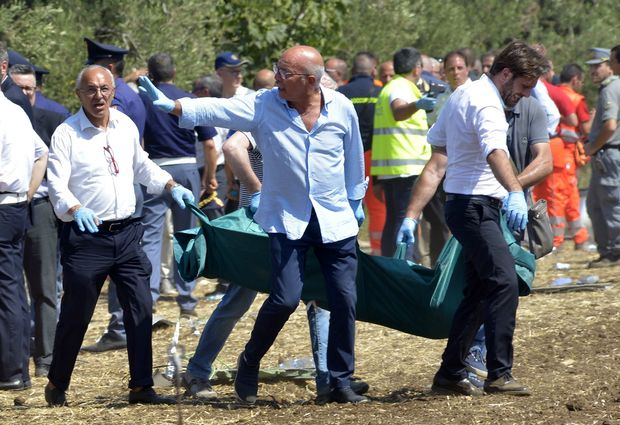 Rescuers carry a coffin after a head-on collision between two trains, near Corato, in the southern Italian region of Puglia on July 12, 2016.