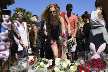 A woman lays a flower in the street of Nice to pay tribute to the victims of the Bastille Day attack.