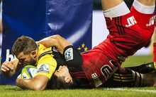 Callum Gibbins scores in the embrace of David Havili.