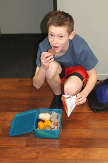 An image of Daniel Bridgman grabbing a quick snack during dance rehearsals.