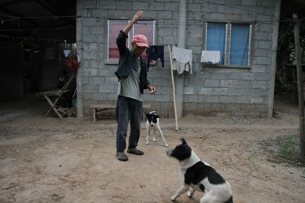 Francisco B. Milallos plays with his dogs as the sun rises