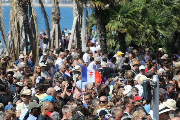 A man holds a French flag showing the Cross of Lorraine as people gather to observe a minute silence on the Promenade des Anglais in Nice on July 18, 2016, in tribute to victims of the deadly Nice attack on Bastille day.
