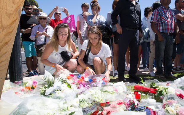 People offer flowers to the victims near the site of the terrorist attack in Nice, France,