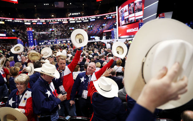 Delegates from Texas wave their hats in the air as the Republican convention begins.