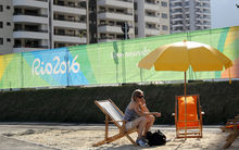 A visitor talks on mobile phone at a fake beach on the entrance of The Olympic Village on Barra da Tijuca neighboorhood, in Rio de Janeiro.