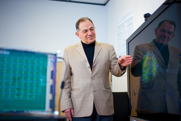 Nikola Kasbov standing in front of a monitor showing a graphical representation of a neural network