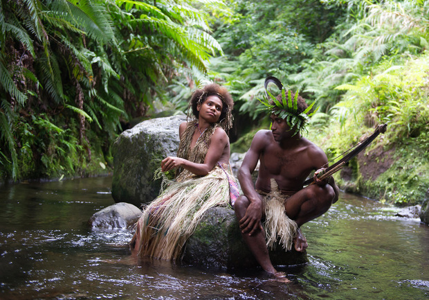 A man and a woman in tradional Ni-Vanuatu clothing sit on a rock in a river