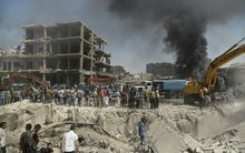 Residents gather at the site of a bomb attack in Syria's northeastern city of Qamishli.