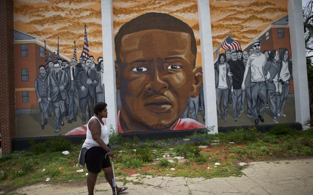 A woman walks past a mural of Freddie Gray in Baltimore.