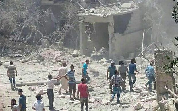 People gather around the area of a damaged building of a maternity hospital after it was hit by an air raid in the rebel-held town of Kafar Takharim.