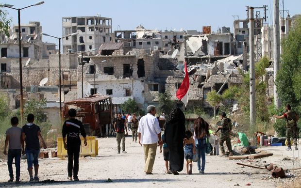 Civilians return to the neighbourhood of Bani Zeid in Aleppo, a day after Syrian government forces took control of the previously rebel-held district.