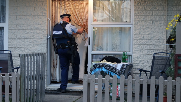 A police officer at the flat in the Christchurch suburb of Hei Hei where a man was shot in the leg.