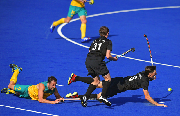 Australia's Mark Knowles and New Zealand's Hayden Phillips and Simon Child vie during the men's hockey match at the Rio Olympics.