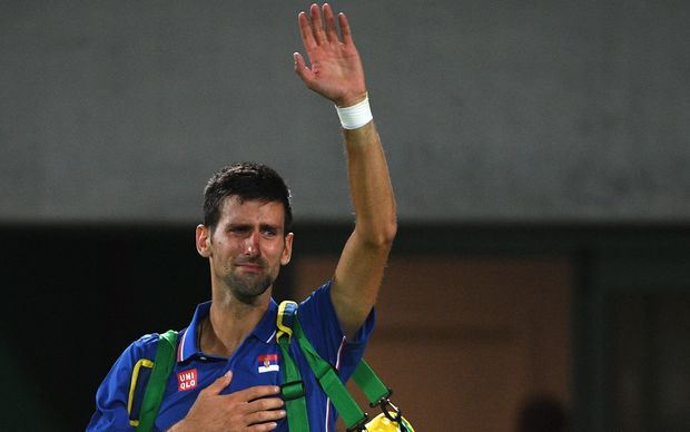 Serbia's Novak Djokovic waves to the crowd with tears in his eyes after losing his men's first round singles tennis match against Argentina's Juan Martin Del Potro at the Olympic Tennis Centre of the Rio 2016 Olympic Games in Rio de Janeiro on August 7, 2016.