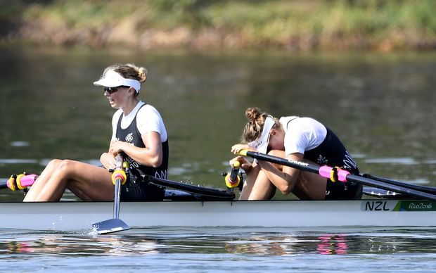New Zealand's Eve Macfarlane and New Zealand's Zoe Stevenson (L) sit on their boat after the Women's Double Sculls semifinal rowing competition