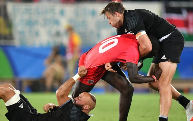 New Zealand's D J Forbes (L) and New Zealand's Tim Mikkelson (R) tackle Kenya's Bush Mwale in the men's rugby sevens match between New Zealand and Kenya during the Rio 2016 Olympic Games.