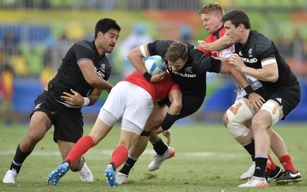 New Zealand's Tim Mikkelson is tackled sevens match against Great Britain.