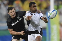 New Zealand's Sam Dickson, left, tackles Fiji's Vatemo Ravouvou in the men's rugby sevens quarter-final match between Fiji and New Zealand at the Rio Olympics.