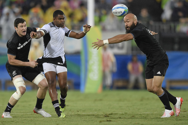 New Zealand's Sam Dickson (L) tackles Fiji's Vatemo Ravouvou (2nd L) as New Zealand's D J Forbes reaches for the ball in the men's rugby sevens quarter-final match between Fiji and New Zealand during the Rio 2016 Olympic Games in Rio de Janeiro on August 10, 2016.