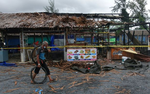 A man walks past the site of a small bomb blast and arson attack on Bang Niang market, Takua Pa, near Khao Lak in Phang Nga province, Thailand.