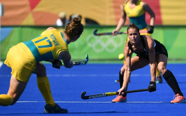 Australia's Georgina Morgan (L) shoots in front of New Zealand's Petrea Webster (R) during the the women's quarterfinal field hockey New Zealand vs Australia match of the Rio 2016 Olympics Games at the Olympic Hockey Centre in Rio de Janeiro on August 15, 2016.