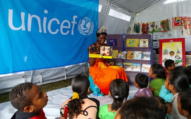 The Reigning Miss Hibiscus 2015, Marie Fall, takes part in a special reading with children of the newly launched locally produced children's story books.