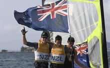 Peter Burling and Blair Tuke celebrate winning the skiff 49ers medal race at the Rio Olympics with coach Hamish Willcox.