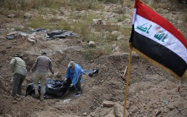 Members of the Iraqi security forces wearing protective clothes inspect a mass grave containing the remains of people believed to have been slain by jihadists of the Islamic State (IS) group at the Speicher camp