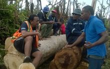 Itu Josaia (L) and the logging team take a break while dragging logs by hand in Nasau Village, Koro Island.