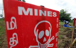 A man de-mines a road behind a warning sign at Sri Lanka,in 2009.