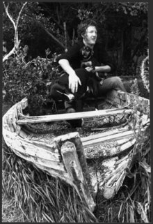 Sam Hunt with a dog and a puppy, sitting on the wreck of a row boat, at an unidentified location. Photograph taken circa 3 December 1975 by an unidentified staff photographer for the Evening Post.