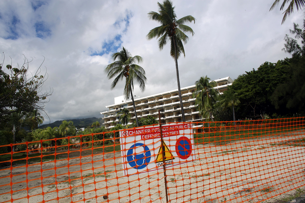 "The planned construction site of the tourism complex ""Mahana Beach"", with the derelict Sofitel Hotel in the background."