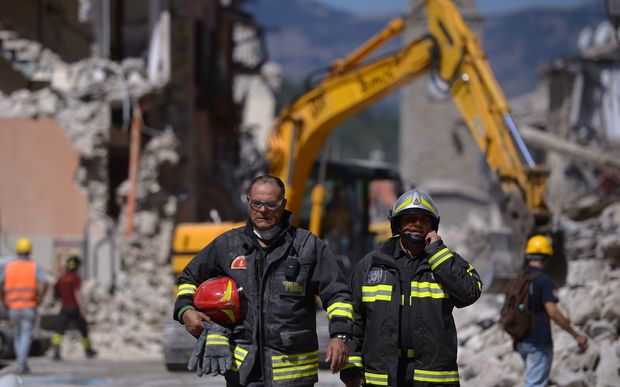 Rescuers coordinate their efforts to free people trapped under the rubble in Amatrice.