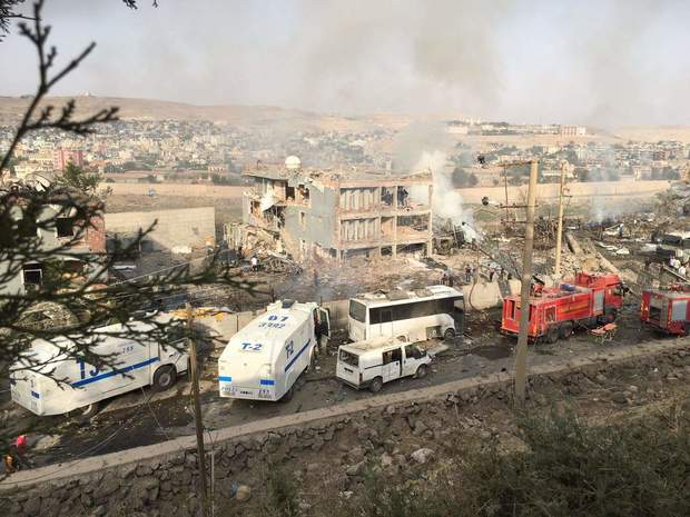 Turkish police and firefighters parked near the damaged police headquarters in Cizre.