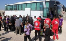 Syrian rebel fighters and their families, helped by Red Crescent, arrive in Idlib after being evacuated from Daraya.