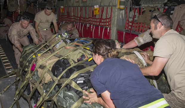 Air Commodore Darryn Webb (top left) helps secure a load on the Air Force C-130 Hercules aircraft.