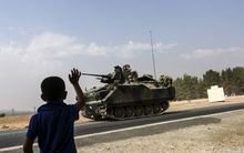 A Turkish boy waves to a Turkish tank driving into Syria from the Turkish Syrian border city of Karkamis in the southern region of Gaziantep, on August 26, 2016.
