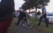 The Facebook video appears to show an officer push the young man off his bike onto the footpath.