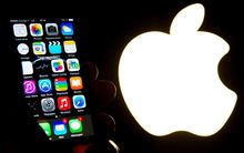 This file photo taken on January 30, 2015 shows a hand holding an iphone next to the Apple logo in Lille.