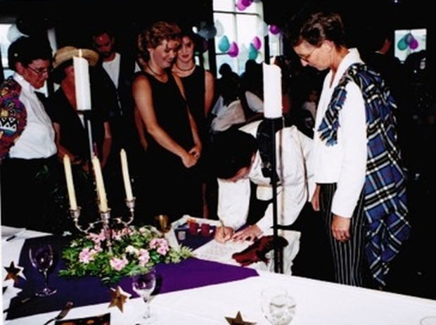 An image of the couple signing the marriage register.